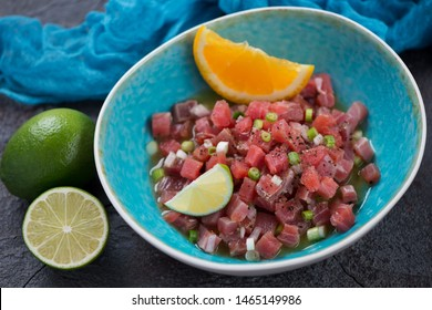 Tuna ceviche cooked with lime and orange juice and served in a turquoise plate, horizontal shot