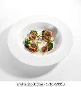 Tuna in crispy breading close up. Served cuisine. Dish with fish fillet and roasted broccoli with spicy sauce in white plate isolated. Restaurant food portion, delicious supper, main course