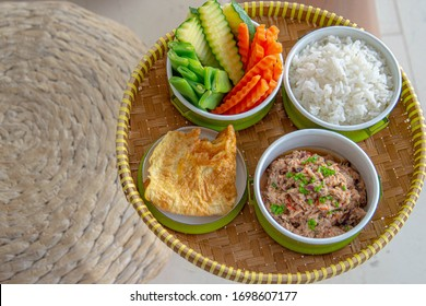 Tuna dip with rice, omelette and vegetables in green tiffin in basket