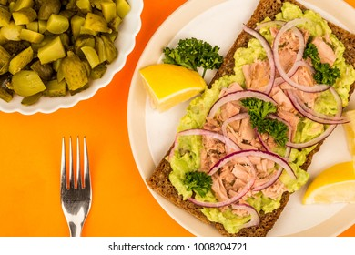 Tuna Fish and Avocado With Onions on Rye Bread Open Face Sandwich Against An Orange Background