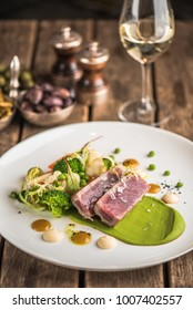 Tuna grill, vegetables in a white plate and a glass of white wine on a wooden table. Seafood is a useful fresh hot meal.