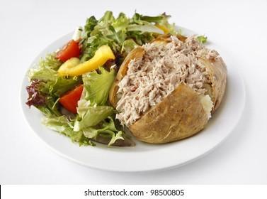 A Tuna Mayonnaise baked potato on a plate with side salad
