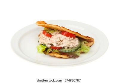Tuna mayonnaise and salad in a folded flatbread on a plate isolated against white