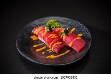 Tuna Nigiri, Sushi Tuna with Spicy Sauce on traditional Japanese food on ceramic dish, Japanese food style, Sushi Menu, sushi tuna, maguro sushi on black dish, selective focus