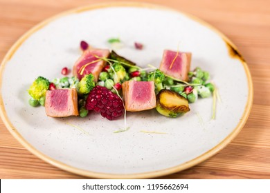 Tuna pieces on plate with brussels sprouts, garnet fruit, green peas. Healthy deliciuos food