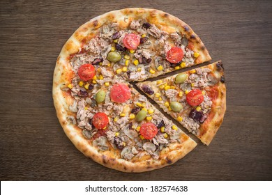 Tuna pizza with vegetables on a wooden table. Healthy replacement for a fast/ junk food version of pizza. Top view.