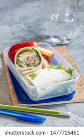 Tuna salad and egg wraps in lunch box with apple