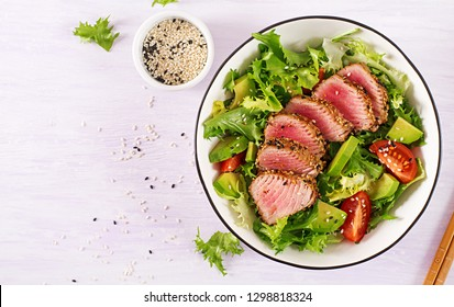 Tuna salad. Japanese traditional salad with pieces of medium-rare grilled Ahi tuna and sesame with fresh vegetable on a bowl. Authentic Japanese food. Top view