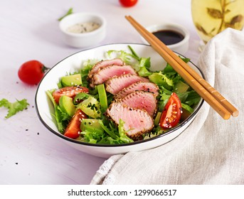 Tuna salad. Japanese traditional salad with pieces of medium-rare grilled Ahi tuna and sesame with fresh vegetable on a bowl. Authentic Japanese food.