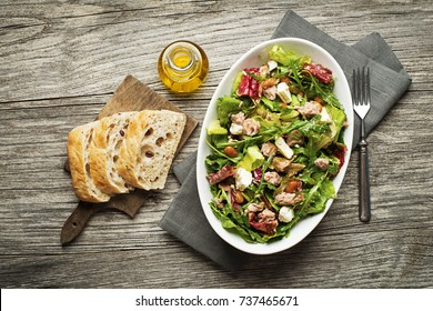 Tuna salad with lettuce, beans and cheese on wooden table