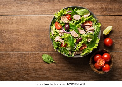 Tuna salad with lettuce, tomatoes and olives on wooden table