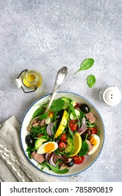 Tuna salad with mix salad leaves (spinach and arugula) , avocado, cherry tomato, cucumber and egg on a light slate, stone or concrete background.Top view.