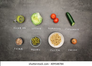 Tuna salad with pasta and vegetables. Top view on recipe ingredients on grey kitchen table with chalky signs.