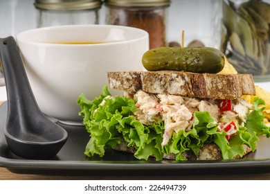 Tuna salad sandwich with lettuce on rye toast with butternut squash soup, potato chips, and a pickle