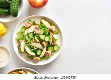 Tuna salad with slices of cucumber, avocado, red apple in bowl over white stone background. Healthy diet food. Top view, flat lay