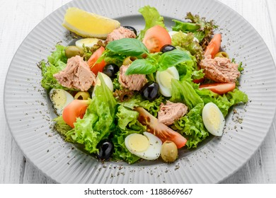 Tuna salad with tomatoes , olives , eggs and onion . On the table