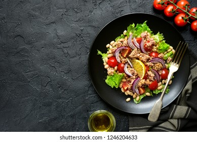 Tuna salad with tomatoes and white bean on a black plate over dark slate, stone or concrete background.Top view with copy space.