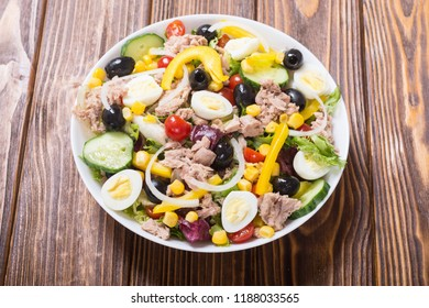 Tuna salad with vegetables , eggs and olives . Healthy food background