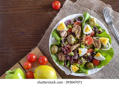 Tuna salad with vegetables and ingredients top view with copy space