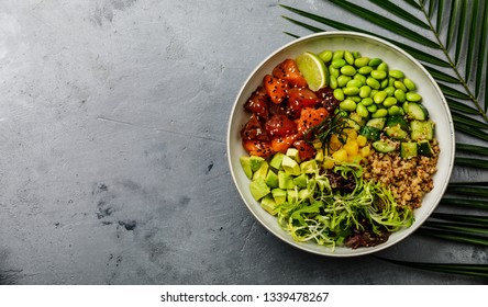 Tuna and Salmon Poke bowl Raw fish salad Asian trendy food with soy beans edamame, quinoa, avocado, pineapple, cucumber and lettuce in bowl on concrete background copy space