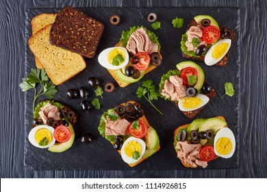tuna sandwiches with avocado slices, lettuce, tomatoes, black olives and hard boiled egg on a rye and corn toasted bread on a black slate tray on a wooden table, view from above, flat lay