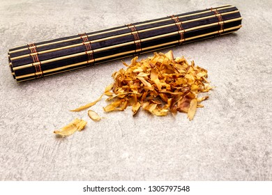 Tuna shaving katsuobushi, bonito flakes, ingredient of japanese soup dashi. On stone background with bamboo mat, close up.