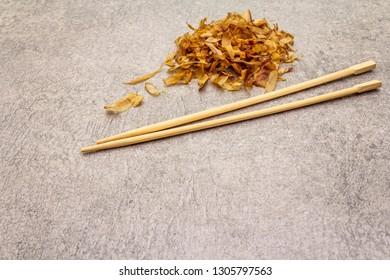 Tuna shaving katsuobushi, bonito flakes, ingredient of japanese soup dashi. On stone background with wooden chopsticks.