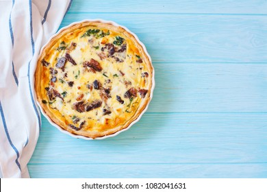 Tuna, Shpinach and Soft Cheese Pie (Quiche) Served on White Pan on Blue Wood Background. Top View