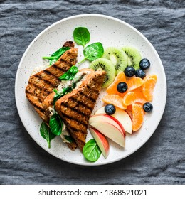 Tuna, spinach, mozzarella hot toast and fresh fruit - delicious healthy breakfast, brunch, snack on a gray background, top view