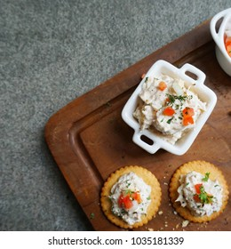 Tuna spread with crackers, and tuna spread in white bowl on wooden plate, top view