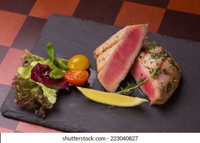 tuna steak garnished with vegetables on stone plate. top view