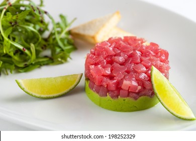 Tuna tartar garnished with lime and arugula isolated on white background