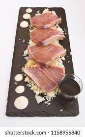 tuna tataki served on an oblong slate with couscous and soy sauce