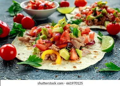 Tuna Tortilla with avocado, fresh salsa, limes, greens, parsley, tomatoes, red yellow pepper. colorful vegetable. Healthy Food