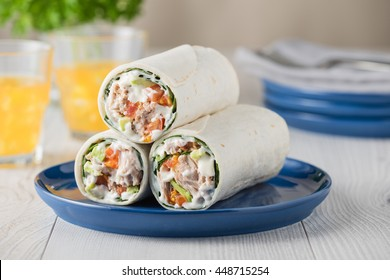 Tuna wraps with avocado tomato and mayonnaise on blue plate