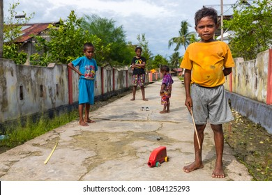 TUNGU VILLAGE, ARU ISLANDS, INDONESIA, DECEMBER 06, 2017 : Kids playing with plastic can cars in the street of Tungu village, Aru islands, Papua, Indonesia.