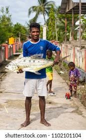 TUNGU VILLAGE, ARU ISLANDS, INDONESIA, DECEMBER 06, 2017 : Proud angler is showing his big fish in the Tungu village, Aru islands, Papua, Indonesia.