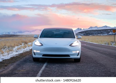 Tungubakkar,  / Iceland March 2nd 2019 : Photograph of a white Tesla model 3 driving on a road in Iceland at sunset.