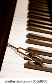 Tuning fork on top of piano keys in sepia color