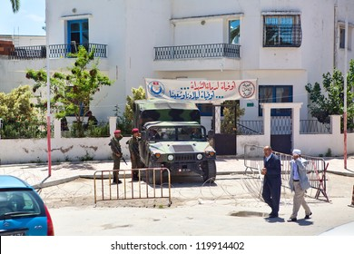 TUNIS CITY, TUNISIA - CIRCA MAY, 2012: Military guards with guns with armored car standing before administration building on circa May, 2012 in Tunis city, Tunisia, Africa.