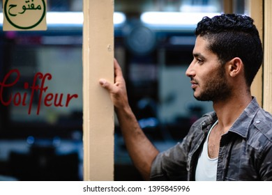 """TUNIS, TUNISIA - APRIL 20, 2019: Handsome and good looking arab male model with dark hair and a small beard, posing in front of a hairdresser, """"coiffeur"""" in French, for a hairstyle shoot"""