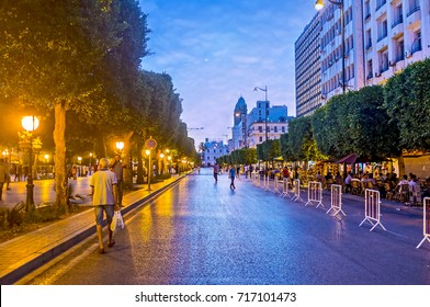 TUNIS, TUNISIA - AUGUST 30, 2015: Evening Habib Bourguiba Avenue is best place to relax in cozy outdoor restaurant, taste local cuisine and enjoy the illuminated city center, on August 30 in Tunis.
