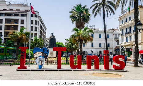 """Tunis, Tunisia, July 01, 2018: Inscription """"I love Tunis"""" and monument to famous medieval historian Ibn Khaldounon at Independence Square."""