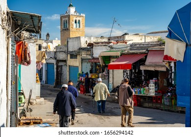 Tunis, Tunisia - Nov 19, 2019: Poor area of the city with shops and a mosque in the background