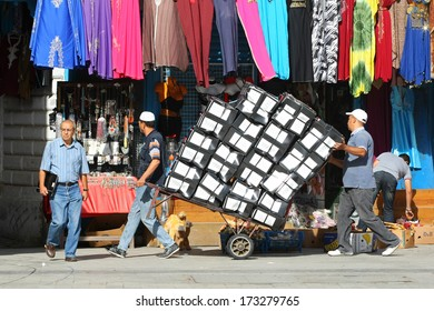 TUNIS, TUNISIA - SEPTEMBER 14 : Two men pushing a trolly full of stacked shoe boxes in the Medina, famous marketplace on September 14th, 2012 in Tunis,Tunisia.