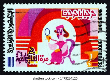 """TUNISIA - CIRCA 1982: A stamp printed in Tunisia from the """"Stories and Songs from Tunisia"""" issue shows Woman admiring herself in mirror, circa 1982."""