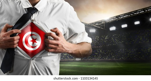 Tunisia soccer or football supporter showing flag under his business shirt on stadium.