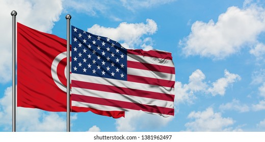 Tunisia and United States flag waving in the wind against white cloudy blue sky together. Diplomacy concept, international relations.