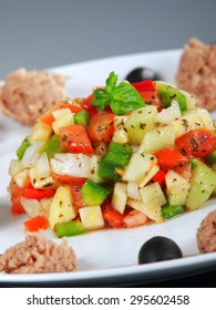 Tunisian salad with tomatos, cucumbers and tuna garnished with fresh basil leaves