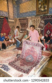 Tunis/Tunisia - September 09 2014: A salesman showing different types of traditional Tunisian carpets to a group of tourists in Tunis